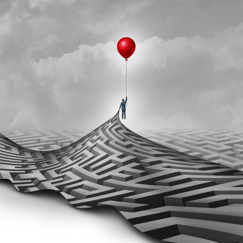 Businessman success concept as a metaphor to overcome obstacles as a person lifting a maze or labyrinth using a red balloon as a symbol for vision and finding a way to succeed.